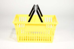 Large yellow plastic shopping basket with double black handgrips top view